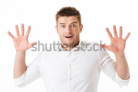 Portrait of a shocked young man looking at camera Stock photo © deandrobot