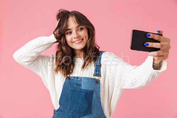 Portrait of a smiling young girl taking a selfie Stock photo © deandrobot