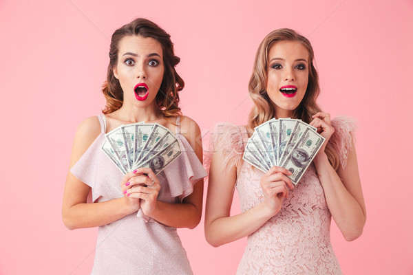 Two excited girls 20s in fancy outfit holding fan of money 100 d Stock photo © deandrobot