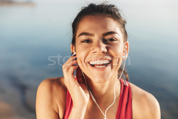 Stock photo: Close up of a happy sportswoman listening to music