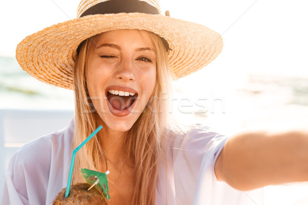 Image of joyful pretty woman 20s in summer straw hat laughing, a Stock photo © deandrobot