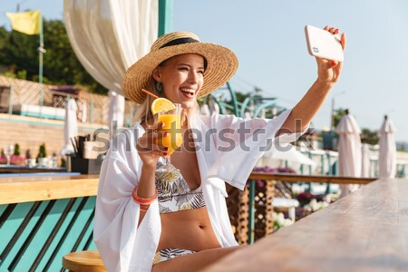 Photo of cheerful young woman 20s in straw hat smiling and takin Stock photo © deandrobot