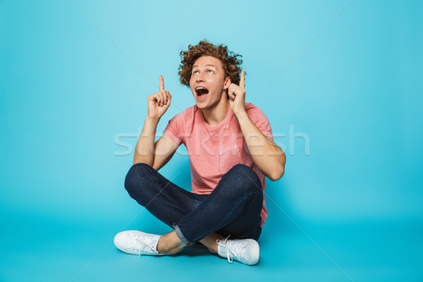 Portrait of a happy young curly haired man Stock photo © deandrobot