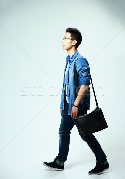 Studio shot of a young asian man walking on gray background Stock photo © deandrobot