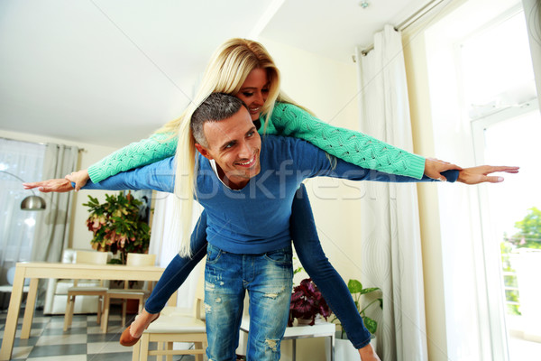 Two young smiling person with the hands lifted upwards at home Stock photo © deandrobot