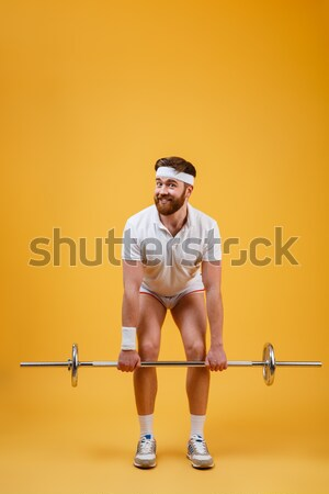 Muscular man doing exercises with barbell over white background Stock photo © deandrobot