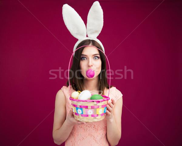 Nő tart tojás ajkak rózsaszín nyuszi Stock fotó © deandrobot