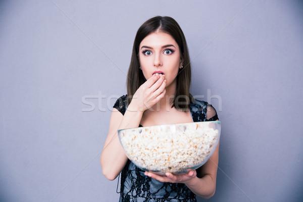 Jovem maravilhado mulher alimentação pipoca cinza Foto stock © deandrobot