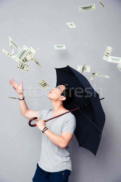 Asian man permanente regen geld paraplu Stockfoto © deandrobot