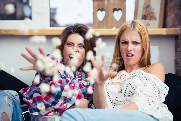 Two woman throwing popcorn Stock photo © deandrobot