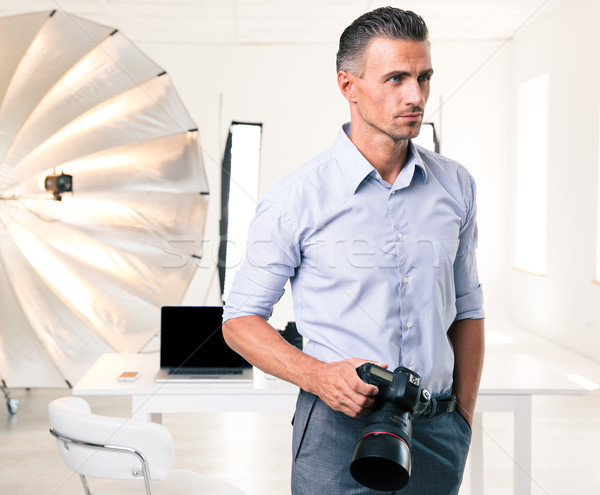 Handsome photographer standing with camera Stock photo © deandrobot