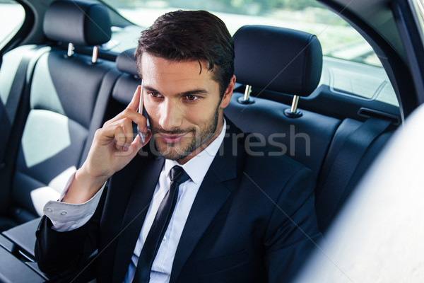 Businessman talking on the phone in car Stock photo © deandrobot