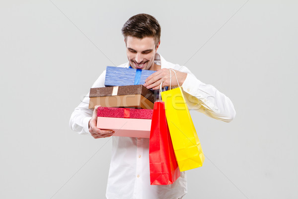 Handsome happy man holding colorful gifts Stock photo © deandrobot