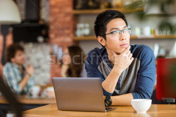 Asian man sitting with laptop in cafe and looking away Stock photo © deandrobot