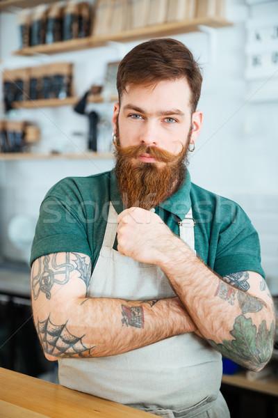 Atraente masculino barista em pé tocante barba Foto stock © deandrobot