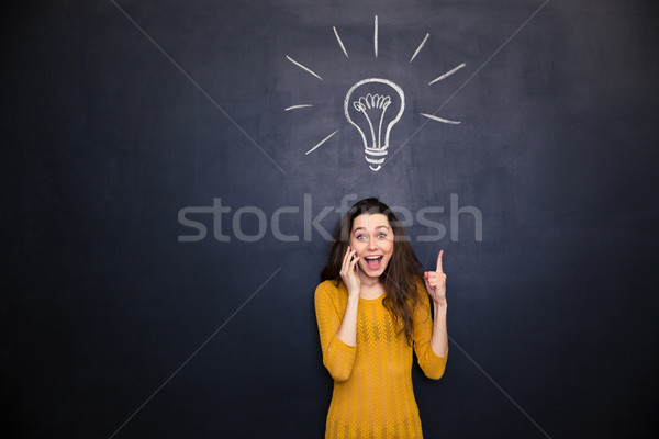 Excited woman pointing on light bulb drawn at blackboard background  Stock photo © deandrobot
