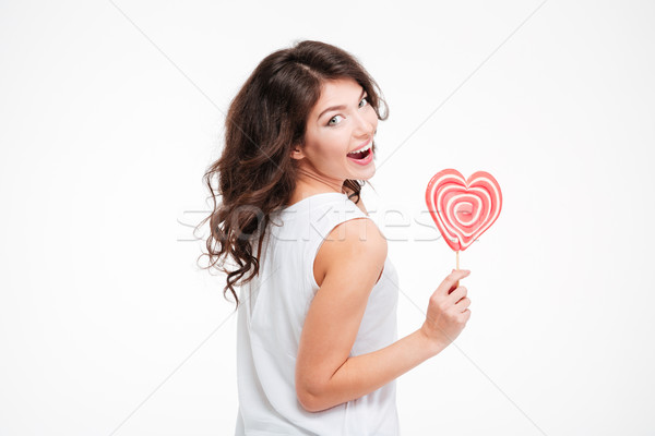 Happy woman holding lollipop and looking back at camera Stock photo © deandrobot