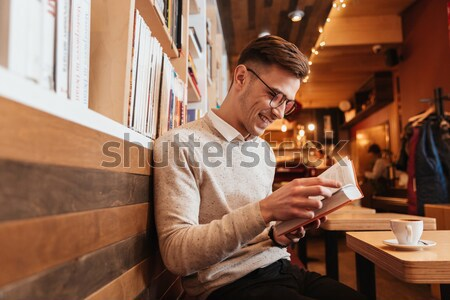 Smiling man eating and talking to girlfriend in wooden cottage Stock photo © deandrobot