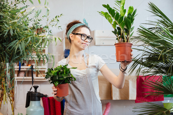 Pensive cute woman florist holding plants in flowerpots and thinking  Stock photo © deandrobot