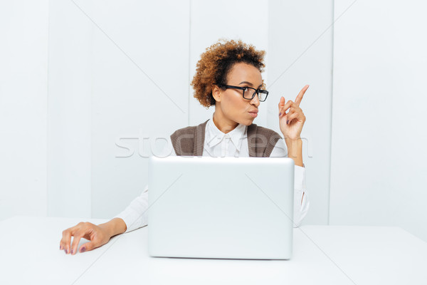 Inspired african american businesswoman pointing up and having an idea  Stock photo © deandrobot