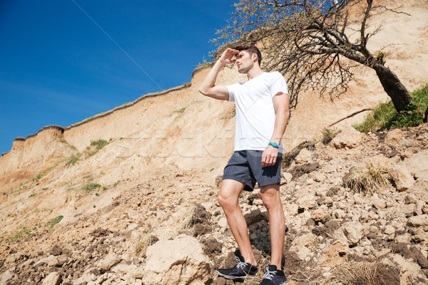Man standing outdoors and looking far away Stock photo © deandrobot