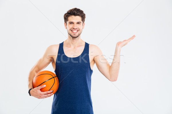 Stock photo: Cheerul young sportsman with basketball ball holding copyspace on palm