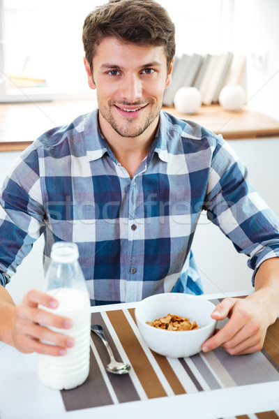 Man eating cereals with milk at the table on kitchen Stock photo © deandrobot