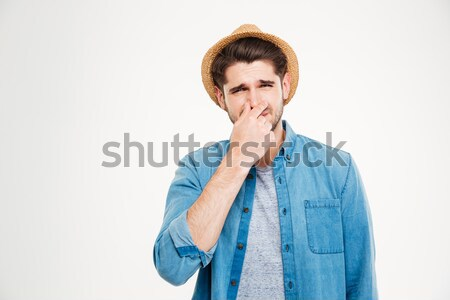 Upset man covered nose by hand and feeling bad smell Stock photo © deandrobot