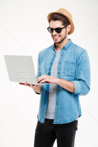 Glimlachend aantrekkelijk jonge man permanente met behulp van laptop zonnebril Stockfoto © deandrobot