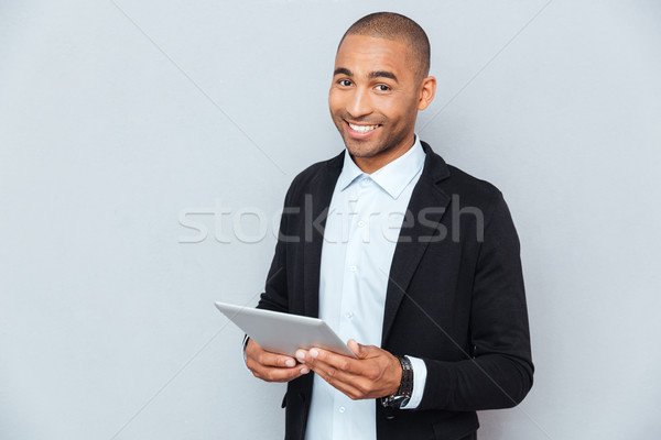 Happy african american young man smiling and using tablet Stock photo © deandrobot