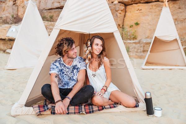 Couple sitting in teepee on the beach Stock photo © deandrobot