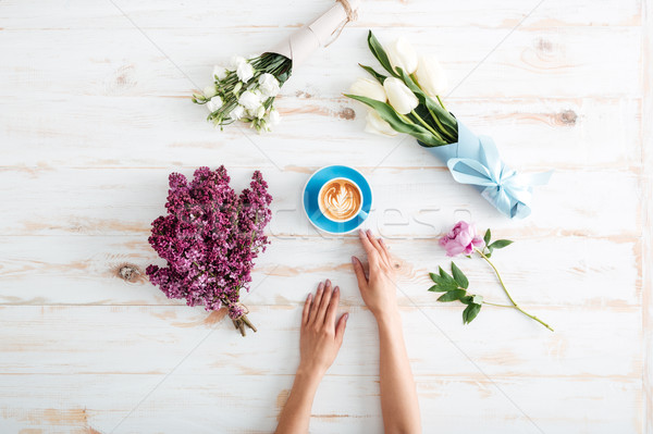 Stock photo: Female hands holding cup of coffee over wooden table