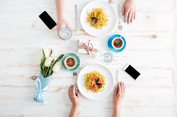 Hands of couple eating pasta and drinking water on table Stock photo © deandrobot