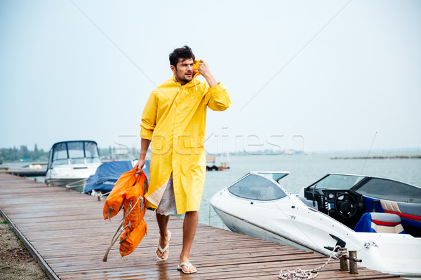 Sailor man in yellow cloak walking at the sea pier Stock photo © deandrobot