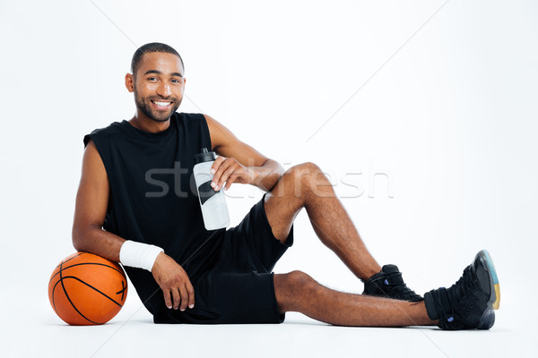 Cheerful young man basketball player sitting and drinking water Stock photo © deandrobot