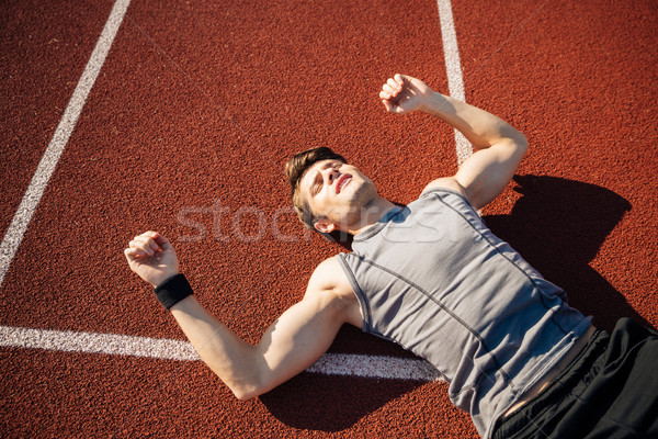 Fitness young man laying on running track after hard workout Stock photo © deandrobot