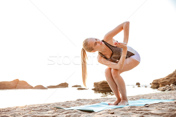 Portrait of a woman standing in yoga pose on beach Stock photo © deandrobot