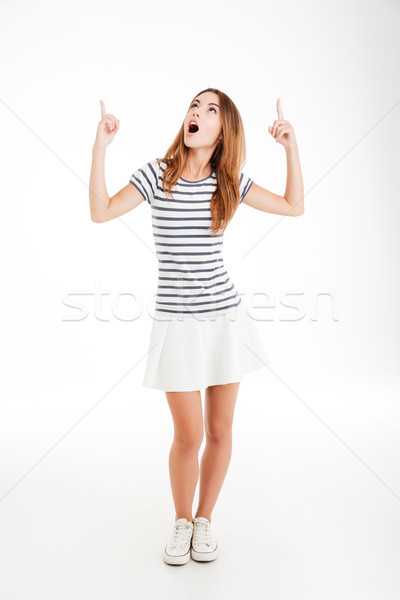 Casual inspired young woman pointing two fingers up Stock photo © deandrobot