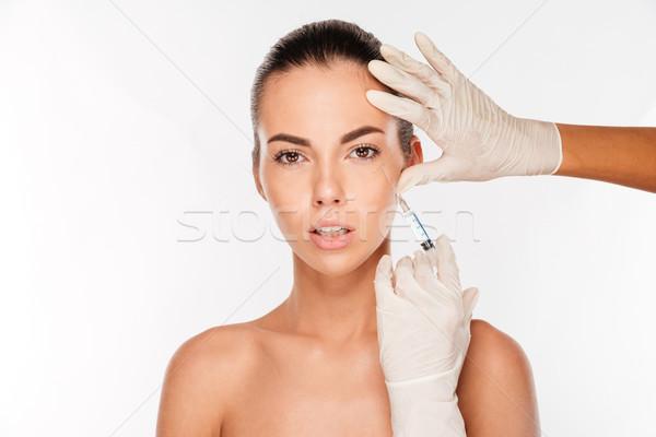 Güzel bir kadın enjeksiyon yüz yalıtılmış beyaz el Stok fotoğraf © deandrobot