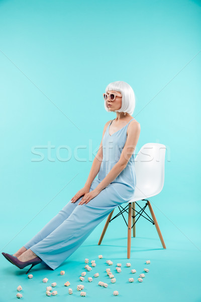 Full length of beautiful woman in sunglasses sitting on chair Stock photo © deandrobot