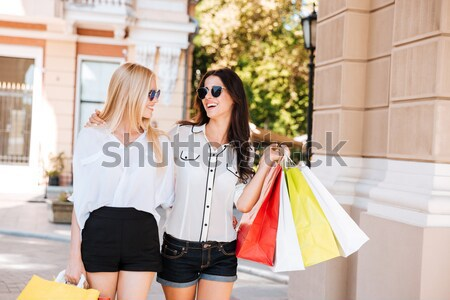 Two attractive women holding paper cups of coffee and chatting Stock photo © deandrobot
