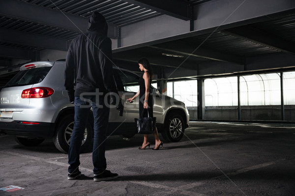 Criminal man looking at young woman opening car on parking Stock photo © deandrobot