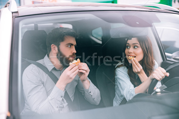 Beauty couple eating in car Stock photo © deandrobot