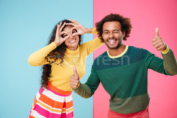 Cheerful amusing african young couple having fun together Stock photo © deandrobot