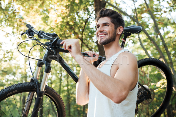 Cyclist holding bicycle in forest Stock photo © deandrobot