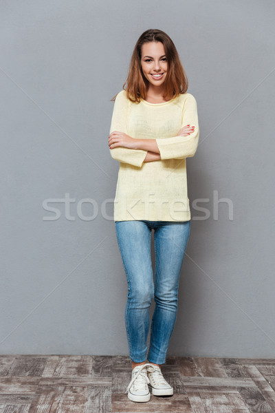 Happy young girl in sweater standing with arms folded Stock photo © deandrobot