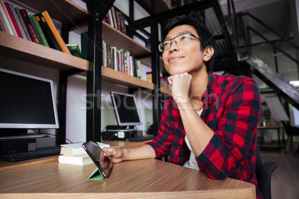 álmodik ázsiai férfi tabletta könyvtár fotó Stock fotó © deandrobot
