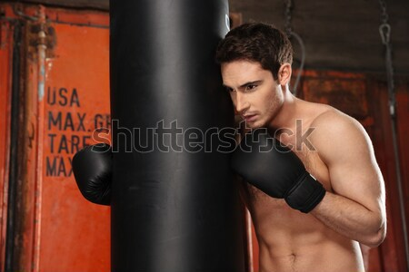 Boxer standing in a gym near punchbag and showing biceps Stock photo © deandrobot