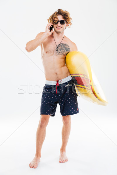 Sportsman holding surfboard and talking on mobile phone Stock photo © deandrobot