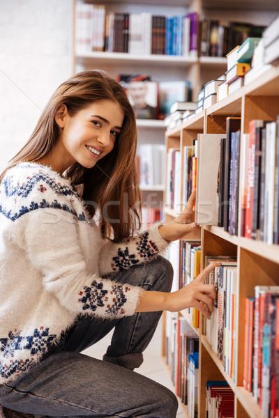 Vrouw naar boeken boekenplank bibliotheek glimlachend Stockfoto © deandrobot